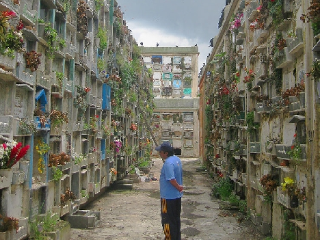 A man stops at a grave in Guatemala City. (Photo by Anthony Fontes.)