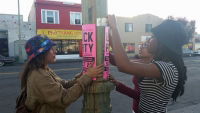 Women hanging block party signs on a light post