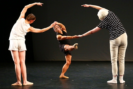Three people dance on a stage under warm light. The people on the right and left arch one arm over their heads toward the center person, who stands with one leg outstreched, parallel to the ground.